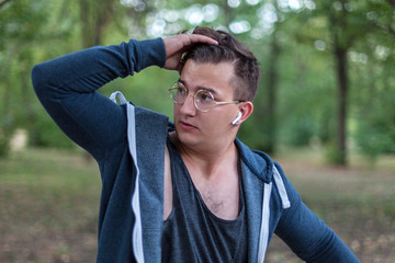 Attractive young caucasian man with golden round glasses touches his dark hair. Serious expression, emotions in the eyes, white headphones (earphones, airpods), silver earring. Outdoors,