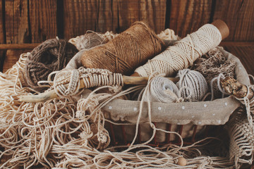 Needlework, macrame, knitting. Yarn and thread of natural colors in a wicker basket. Women's hobby.