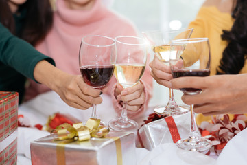 Hands of people celebrating New year party in home with wine drinking glasses and present background. New year and Christmas party concept. Happiness and Friendship and Funny together. Clinking glass