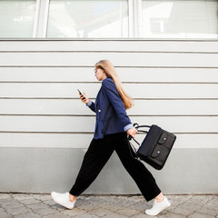 Business woman running in a suit with a briefcase along the wall.