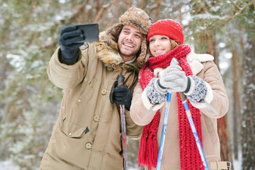 Waist up portrait of active young couple taking selfie photo via smartphone while enjoying skiing in snowy winter forest during date