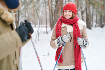 Waist up portrait of beautiful young woman smiling and looking at boyfriend while enjoying skiing in beautiful winter forest, copy space