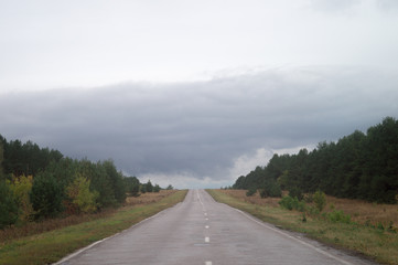 Overcast October highway. Way beyond the horizon, route under heavy leaden sky
