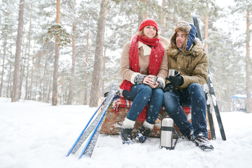 Full length portrait of active young couple  enjoying hot cocoa during ski date in beautiful winter forest, copy space
