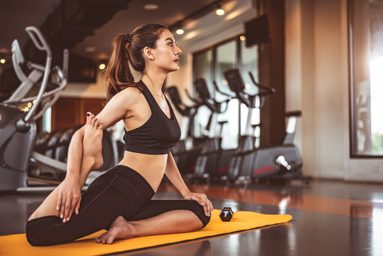 Woman doing bending legs yoga in fitness workouts training gym center background. Lifestyle woman sitting with sport dumbbell equipment and exercise treadmill background. Yoga girl in black sports bra