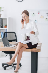 businesswoman working with documents and talking on smartphone while sitting on table with laptop
