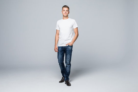 Full height of young happy casual man walking forward to the camera on white backround