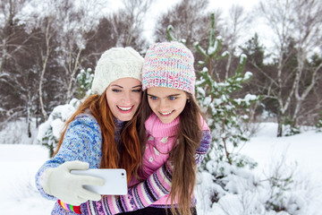 Mom and daughter are photographed in a winter forest, family values. Two girls make a photo. Selfie on phone in winter. Family of mother and her  daughter outdoors on beautiful winter day with snow.