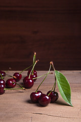 Red sweet cherry with green leaf on wooden background.