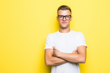 Portrait of a smiling man standing with arms folded isolated over yellow background