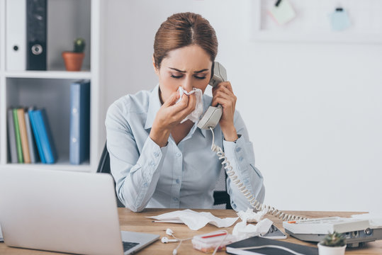 close-up portrait of ill adult businesswoman with runny nose talking by wired phone at office