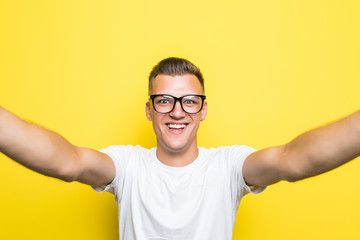 Portrait of a happy man taking a selfie isolated over yellow background