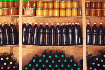Traditional homemade summer wines in bottles on shelves with honey jars. Autumn countryside fair sale.