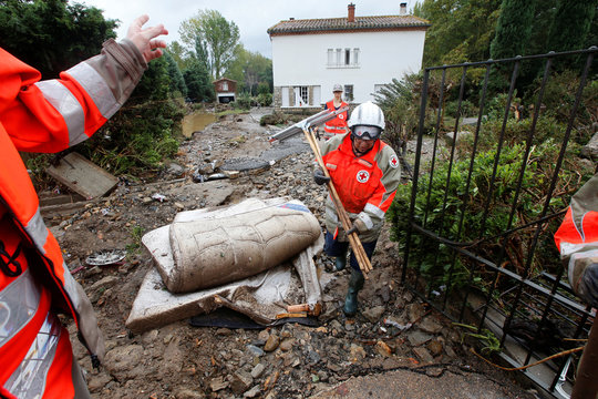 Red Cross workers remove debris as clean-up operations continue the day after some of the worst flash floods in a century turned rivers into raging torrents that engulfed homes and swept away cars hit the southwestern Aude district of France, in Conques
