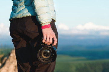 Close-up DSLR camera in the hands of the girl photographer in nature with a camera in hand. Side view