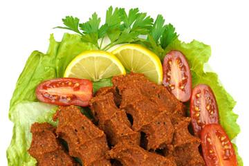 Cig kofte , tradtional Turkish hot spicy bulgur meatballs . Turkish cuisine. Isolated on white background.