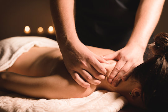 Male manual worker doing spa massage of shoulders and neck to young girl in dark room