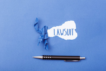 Lawsuit word behind ripped piece of paper