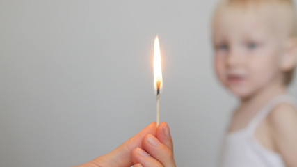 adult's hand holding a burning match in the background portrait of a child, fire, concept, close-up, copy-space, white background, lucifer match
