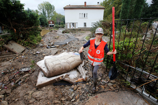 A Red Cross worker removes debris as clean-up operations continue the day after some of the worst flash floods in a century turned rivers into raging torrents that engulfed homes and swept away cars hit the southwestern Aude district of France, in Conques