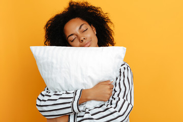 Sleeping. Dreams. Woman portrait. Afro American girl in pajama is hugging a pillow, on a yellow background