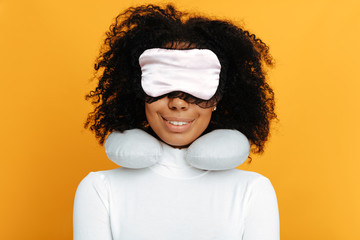 Comfort sleep. Woman portrait. Afro American girl in sleep mask and with a neck pillow is smiling, on a yellow background