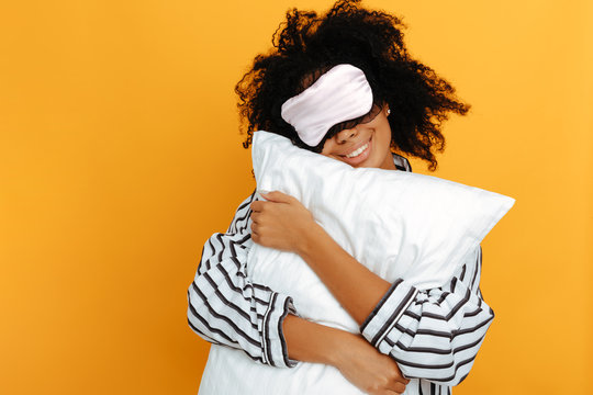 Sleeping. Dreams. Woman portrait. Afro American girl in pajama and sleep mask is hugging a pillow and smiling, on a yellow background