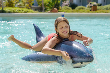 girl swimming in the pool on an inflatable shark