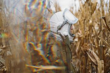 Boy wearing old space helmet lost in the field