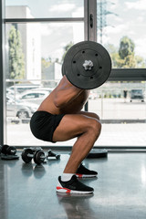 side view of young athletic man lifting barbell in gym