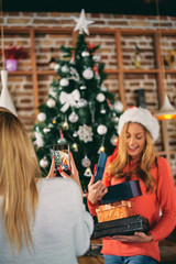 Woman standing and holding gifts in front of Christmas tree while her girlfriend taking photo. Christams holidays concept.