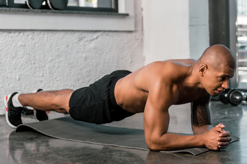 muscular african american sportsman doing plank on fitness mat at gym