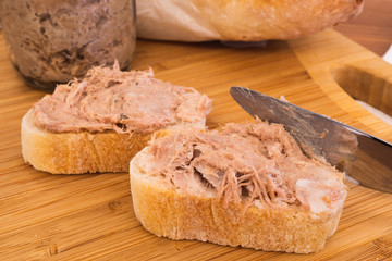 Two Homemade Rillettes French meat spread made of pork on baguette bread and knife spreading the Rillettes