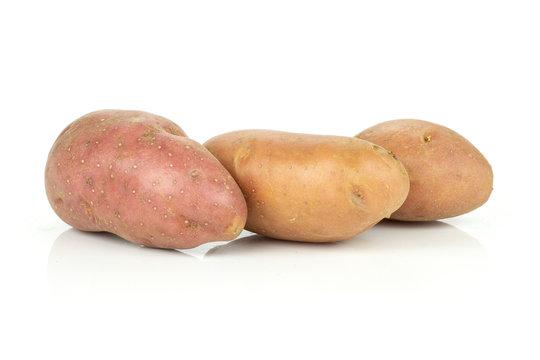 Group of three whole raw fresh red potato francelina variety isolated on white background