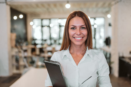 Headshot of young smiling businesswoman. Looking at camera.