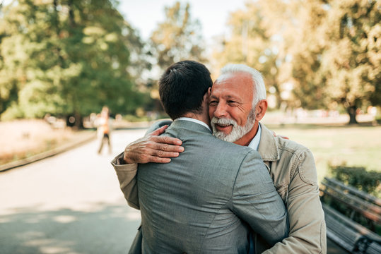 Elderly father and adult son hugging in the park.