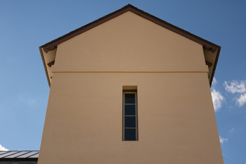 mission style stucco building with a slot window against a cloudy blue sky background