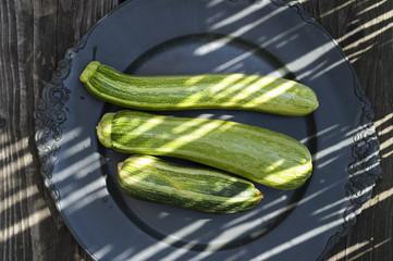 drei Gartenzucchinis auf einem schwarzen Teller