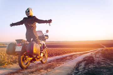Motorbiker travelling, autumn day, motorcycle off road, the driver stands with open arms to the side, to meet a new day, adventurer, extreme tourism, cold weather clothes, light tinting Wall mural