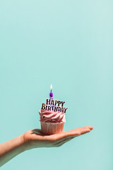 Woman's hand holding birthday cupcake with candle.