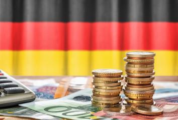 Fotomurales - Geldscheine und Münzen vor der Nationalflagge Deutschlands