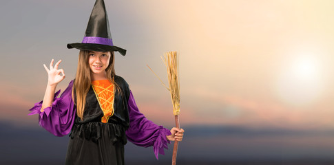 Little girl dressed as a witch for halloween holidays showing an ok sign with fingers at outdoor with sunset