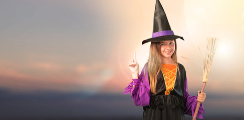Little girl dressed as a witch for halloween holidays counting number one sign at outdoor with sunset