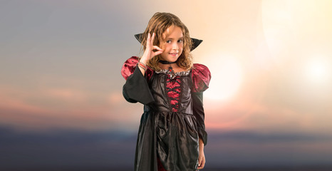 Kid dressed as a vampire at halloween holidays showing an ok sign with fingers at outdoor with sunset