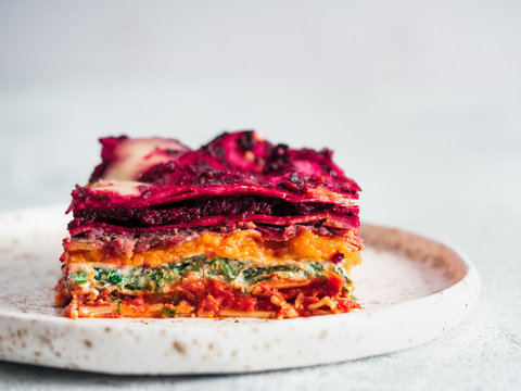 Vegetable Packed Rainbow Lasagne on craft plate. Ideas and recipes for healthy vegetarian dinner or lunch. Lasagne with beetroot, pumpkin, mushrooms, ricotta, spinach, mozarella. Copy space for text.