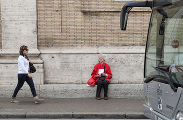 A woman collecting money is seen in downtown Rome