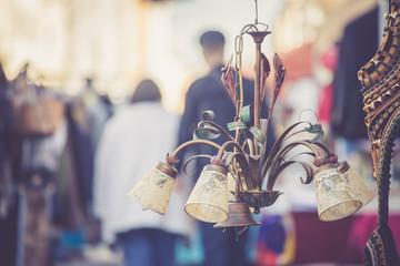 Alte Lampe/Deckenleuchte am Flohmarkt, geschäftige Menschen im Hintergrund Wall mural