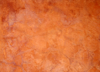 old bright orange brown painted faded stained cracked rough plaster wall background
