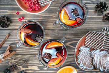Three cups of christmas mulled wine  and cookies on plate on rustic table top view. Traditional drink on winter holiday