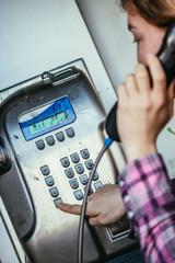 Junges Mädchen telefoniert in alter Telefonzelle, Münztelefon